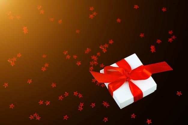 Weiße geschenkbox mit einem roten band und einem zerstreuen von sternen auf schwarzem hintergrund. Premium Fotos