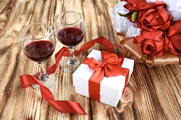 Weiße geschenkbox mit roter satinbandschleife, zwei glas wein und strauß roter und weißer künstlicher rosenblumen auf hölzernem hintergrund. Premium Fotos