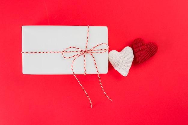 Weiße geschenkbox mit torsion nahe spielzeugherzen Kostenlose Fotos