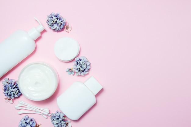 Weiße gläser kosmetik mit blumen auf rosa Premium Fotos