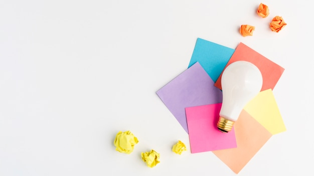 Weiße glühlampe auf bunter klebender anmerkung mit gelb zerknittertem papier Premium Fotos