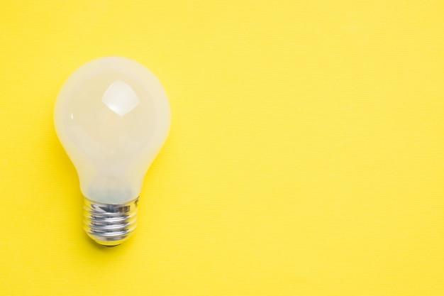 Weiße glühlampe auf hellem gelbem hintergrund mit kopienraum selektiver fokus. Premium Fotos