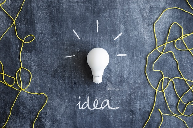 Weiße glühlampe mit text der geschriebenen idee und wolle verlegen auf tafel Kostenlose Fotos