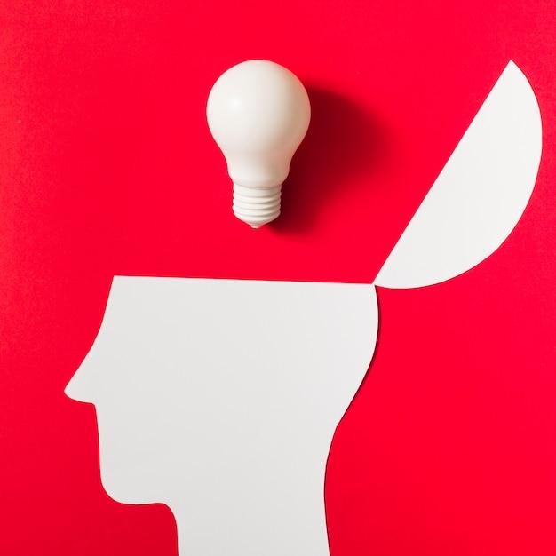 Weiße glühlampe über dem geöffneten papier schnitt kopf gegen roten hintergrund aus Kostenlose Fotos
