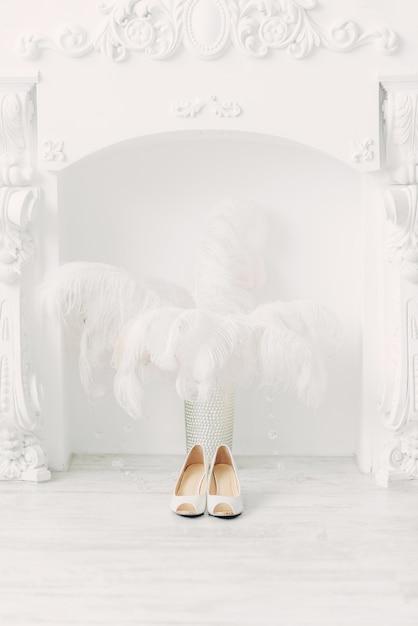 Weiße hochzeitsschuhe über dem kamin und straußenfedern im weißen innenraum Premium Fotos