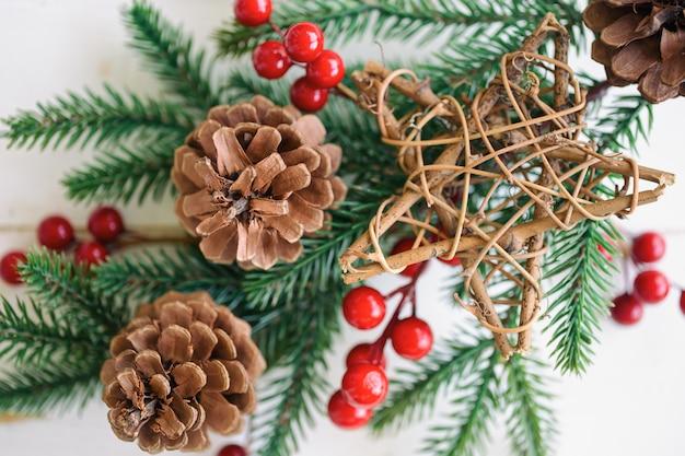 Weiße hölzerne beschaffenheit mit kiefernblatt, kiefernkegeln oder nadelbaumkegel, roten stechpalmenbällen und hölzernem stern im weihnachtskonzept. hölzerner plankenhintergrund in der draufsichtebenenlage mit kopienraum für weihnachtstapete. Premium Fotos