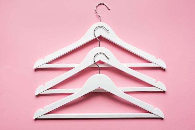 Weiße hölzerne kleiderbügel auf rosa Premium Fotos