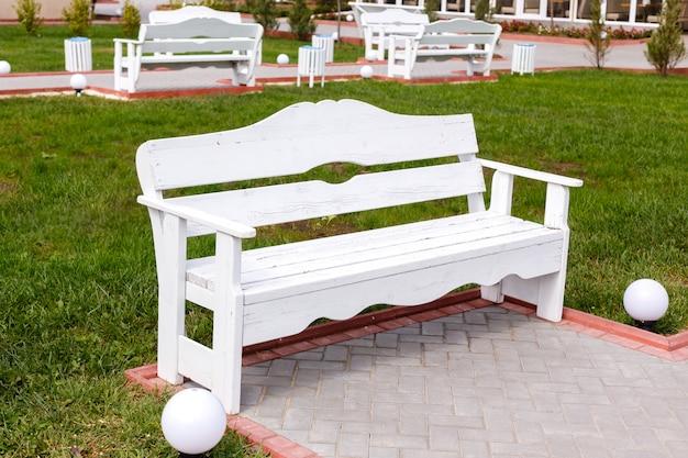 Weiße hölzerne leere bänke im stadtpark. ein guter ort, um an einem sommertag zu entspannen. Premium Fotos