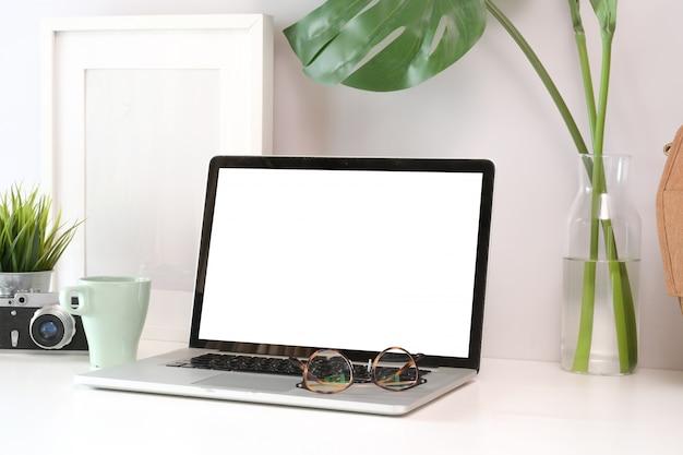 Weiße hölzerne schreibtischtabelle des dachbodens mit laptop- und fotografversorgungen Premium Fotos