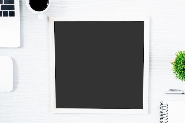 Weiße hölzerne schreibtischtabelle und -ausrüstung für das arbeiten mit kaffee und leerem brett in der draufsicht und im flachen strahlenkonzept. Premium Fotos
