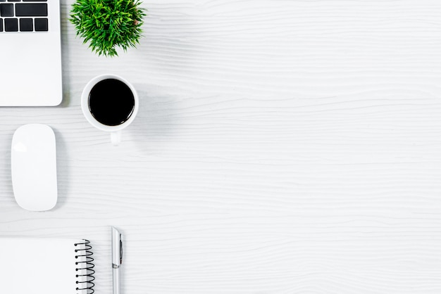 Weiße hölzerne schreibtischtabelle und -ausrüstung für das arbeiten mit schwarzem kaffee in der draufsicht und im flachen strahlnkonzept. Premium Fotos