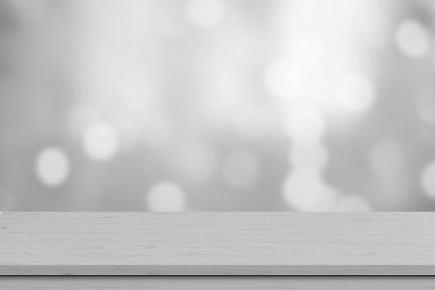 Weiße hölzerne tischplatte über unschärfe weißem bokeh lichthintergrund. leeres hölzernes regal für produktanzeige, -fahne oder -modell. Premium Fotos