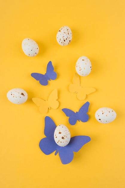 Weiße hühnereien mit papierschmetterlingen auf tabelle Kostenlose Fotos