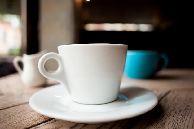 Weiße kaffeetasse der tradition auf holztisch Kostenlose Fotos