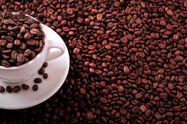 Weiße kaffeetasse gefüllt mit gerösteten bohnen Kostenlose Fotos
