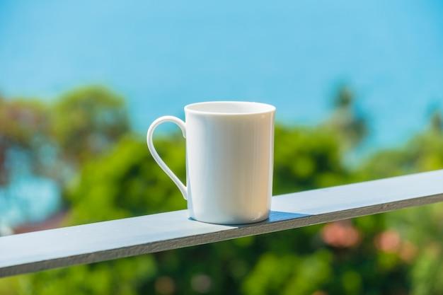 Weiße kaffeetasse mit meerblick Kostenlose Fotos