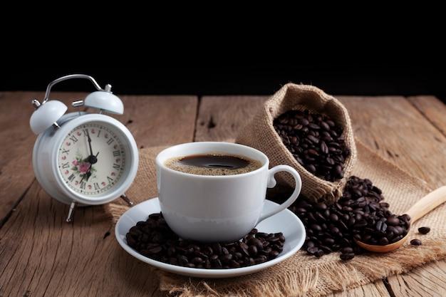 Weiße kaffeetasse mit weißem wecker und kaffeebohnen auf altem hölzernem plankenhintergrund Premium Fotos