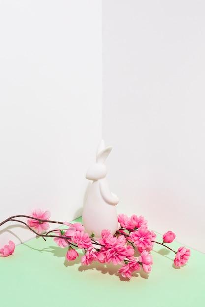 Weiße kaninchenfigürchen mit blumenniederlassung auf tabelle Kostenlose Fotos