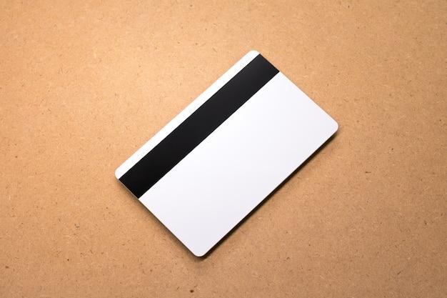 Weiße karte auf hölzernem hintergrund. vorlage der leeren kreditkarte für ihr design. Premium Fotos