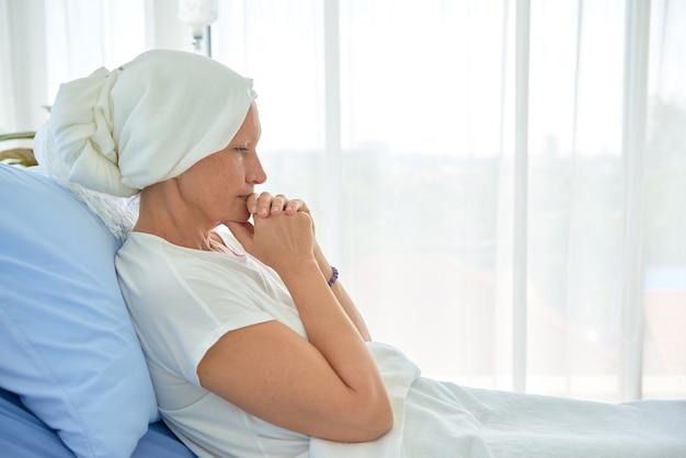 Weiße kaukasische weibliche haarlose und augenbrauenlose fühlen sich schlecht, beten und warten auf chemotherapie im krankenzimmer, brustkrebsbewusstseinsmonatskonzept. Premium Fotos