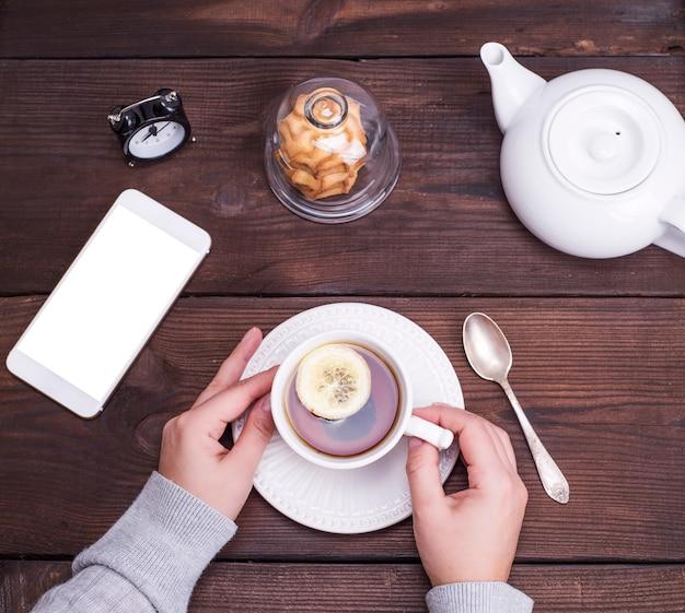 Weiße keramik tasse mit schwarzem tee und zitrone Premium Fotos