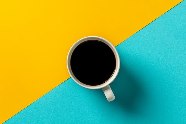 Weiße keramikkaffeetasse auf gelbem und blauem schreibtisch. Premium Fotos