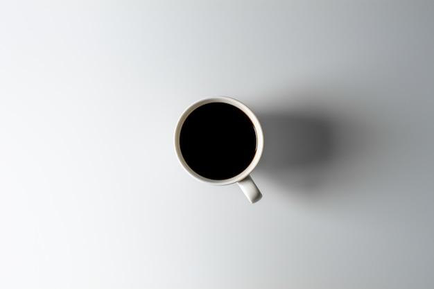 Weiße keramikkaffeetasse auf weißem schreibtisch. Premium Fotos