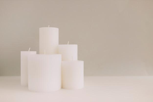 Weiße kerzen auf tischplatte gegen farbigen hintergrund Kostenlose Fotos