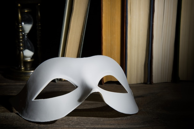 Weiße klassische karnevalsmaske auf buchhintergrund mit weinlesesanduhr auf holztisch Premium Fotos
