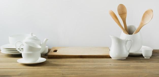 Weiße küchengeräte, geschirr und anderes unterschiedliches weißes material für das dienen auf weißem hölzernem brett. Premium Fotos