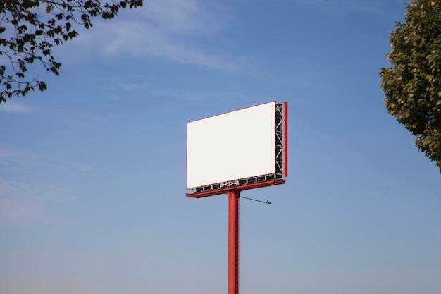 Weiße leere anschlagtafel für anzeige gegen blauen himmel mit bäumen Kostenlose Fotos