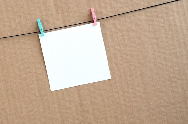 Weiße leere karte auf seil auf einem braunen papphintergrund Premium Fotos