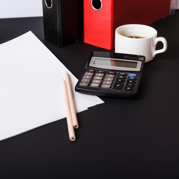 Weiße leere papiere; bleistifte; papierakten; kaffeetasse und taschenrechner auf schwarzem schreibtisch Kostenlose Fotos