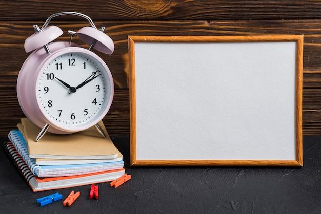 Weiße leere tafel; wecker; wäscheklammer und notizbücher auf schwarzem schreibtisch Kostenlose Fotos