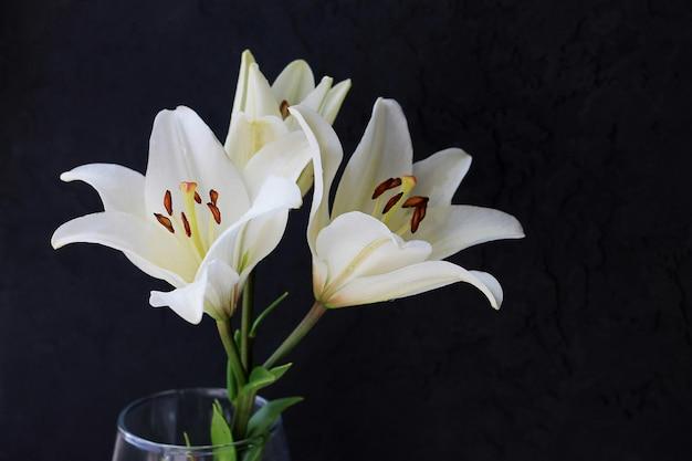 Weiße lilie blüht blumenstrauß auf schwarzem hintergrund. Premium Fotos