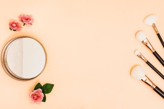 Weiße make-upbürsten mit kompaktem puder und rosen auf farbigem hintergrund Kostenlose Fotos