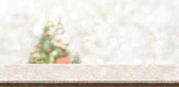 Weiße marmortischplatte am unschärfe bokeh weihnachtsbaumdekor mit lichterkettenhintergrund Premium Fotos