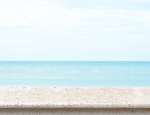 Weiße marmortischplatte mit unscharfem meer und blauem himmel am hintergrund Premium Fotos