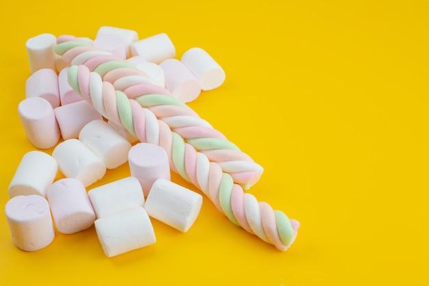 Weiße marshmallows der vorderansicht süß auf gelb Kostenlose Fotos