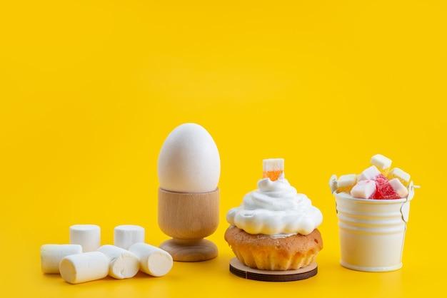 Weiße marshmallows der vorderansicht zusammen mit kuchen und süßigkeiten auf gelbem schreibtisch, süße keksfarbe der zuckersüßigkeit Kostenlose Fotos