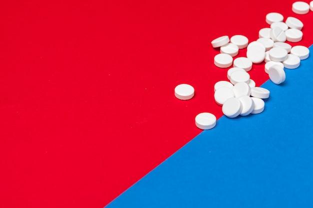 Weiße medizinische pillen auf einem zwei farbroten und blauen hintergrund Premium Fotos