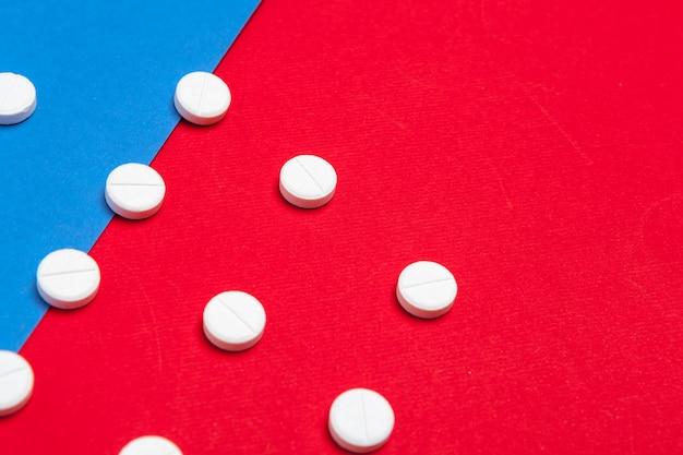 Weiße medizinische pillen auf zwei färben rot und blau Premium Fotos