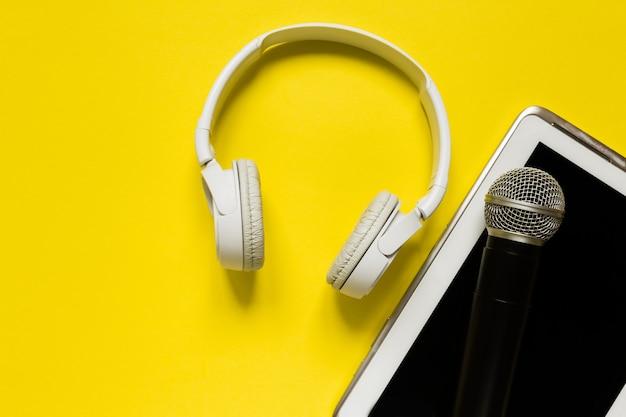 Weiße moderne kopfhörer und tablette auf tendenzgelb backgound ebene legen draufsichtraum für text Premium Fotos