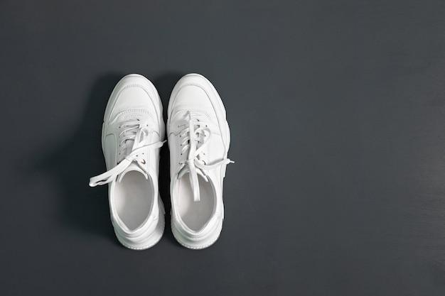 Weiße modische turnschuhe für frauen auf grauer oberfläche Premium Fotos