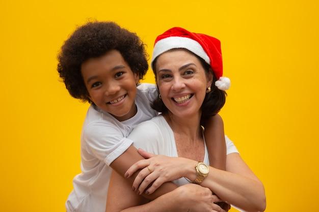 Weiße mutter mit dem schwarzen sohn, der geschenke am weihnachtsabend austauscht. pflegekind sozialer respekt, hautfarbe, inklusion. Premium Fotos