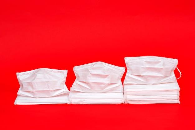Weiße operationsmasken auf rot. statistisches konzeptdiagramm, das den erhöhten verbrauch von masken zeigt Premium Fotos