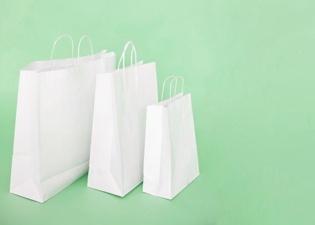 Weiße papiertüten auf hellblauem hintergrund Premium Fotos