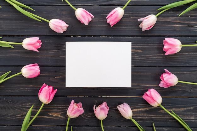 Weiße pappe mitten in rosa tulpen. frühlingskonzept Premium Fotos