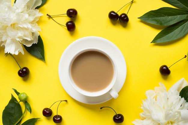 Weiße pfingstrose blüht kirschbeeren tasse kaffee auf gelbem hellem hintergrund. Premium Fotos