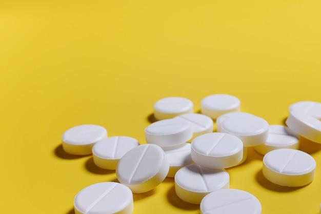 Weiße pillen auf gelbem grund. das konzept von medizin, pharmazie und gesundheit. Premium Fotos